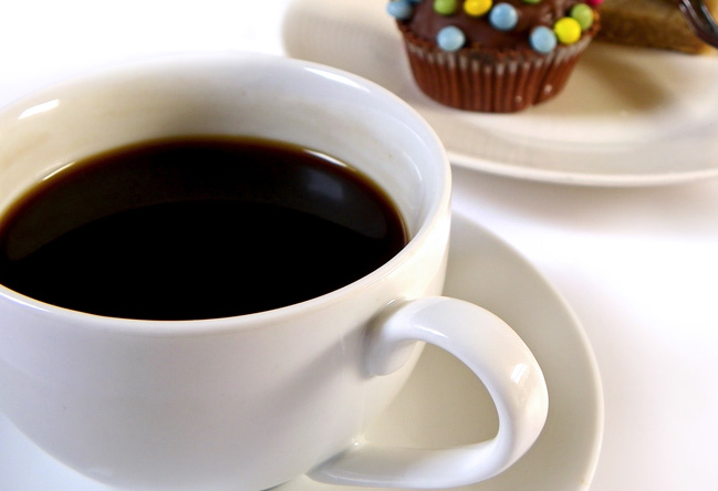 Cup of coffee with saucer and cupcakes in background