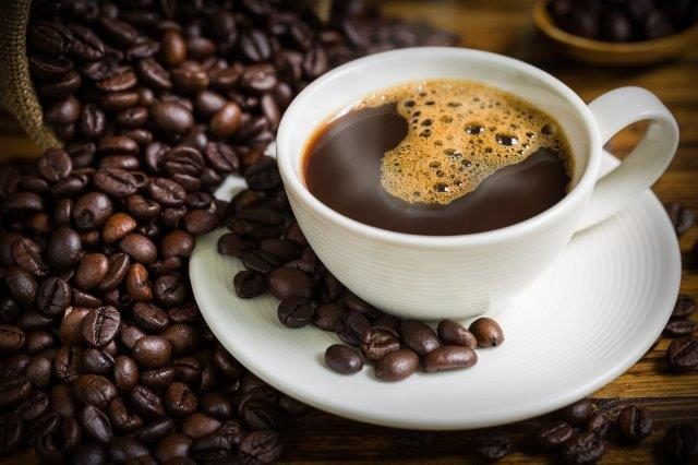 Cup of coffee with saucer and coffee beans